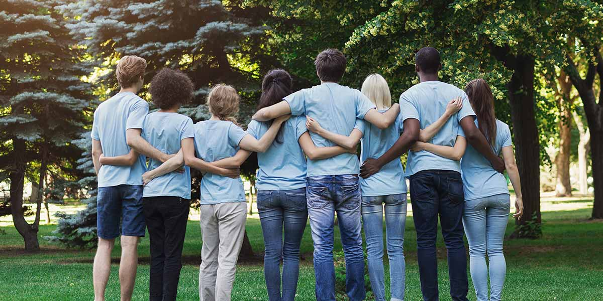 Photo of a group of volunteers in blue shirts standing with their arms around each other, facing away from the camera