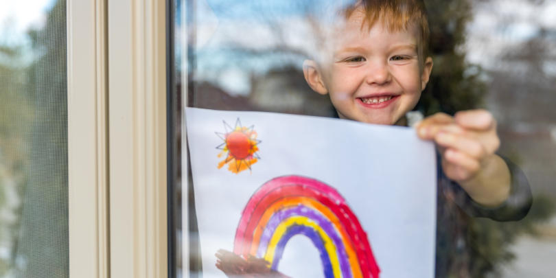 young boy holding a picture of a rainbow up to a window