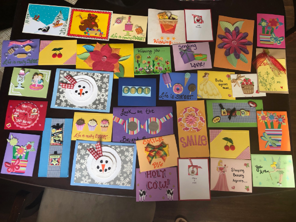 photo of lots of handmade cards sitting on a table with encouraging notes like sending love