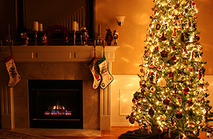 christmas tree and stockings by fireplace
