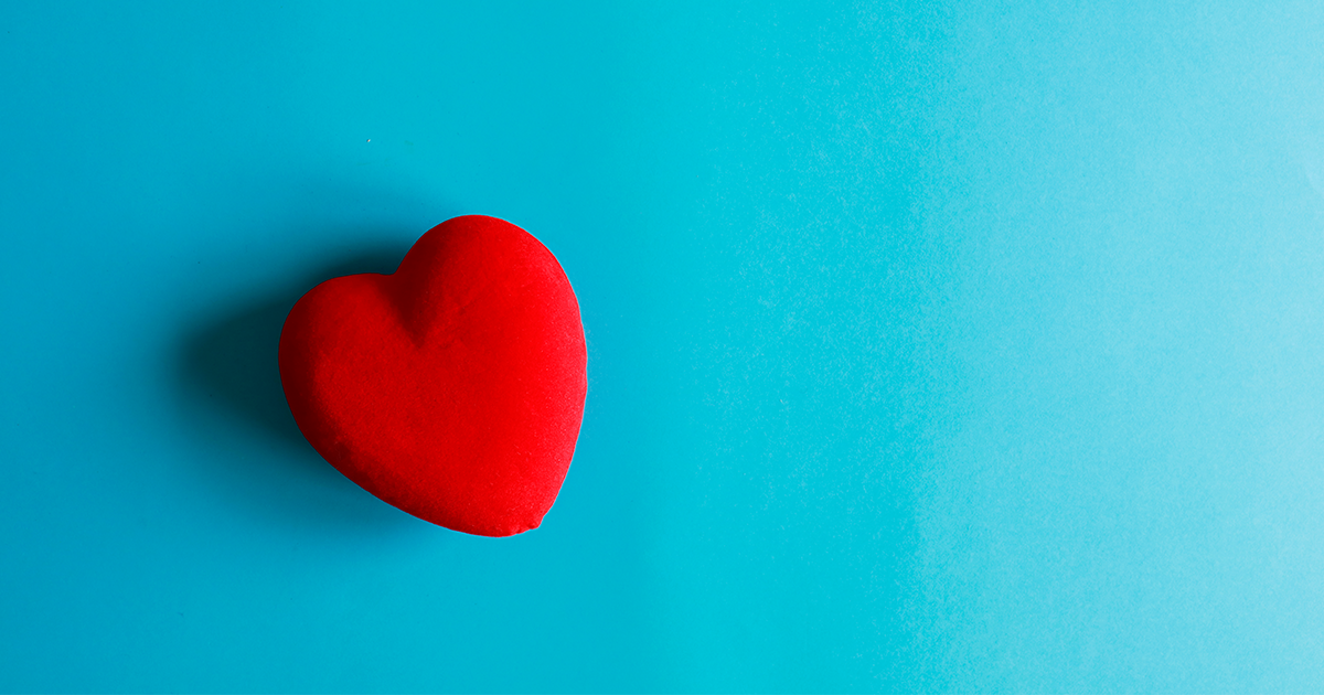 red fabric heart on a bright blue background