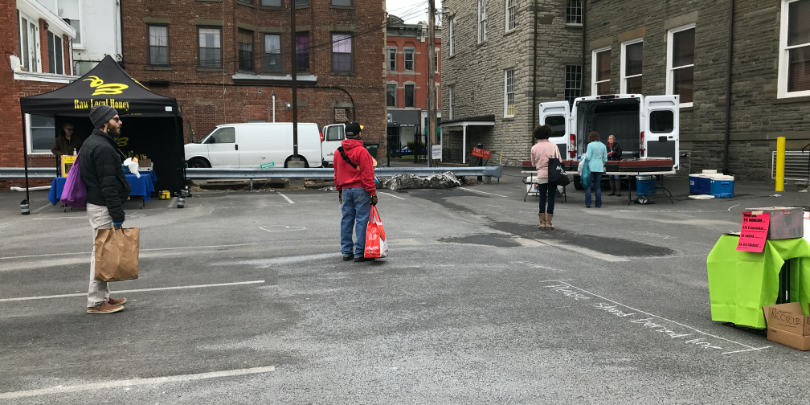 people standing in line six feet apart at kingston farmers market