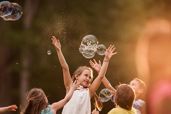 One smiling girl in a group of kids jumps up into the air catching glistening bubbles.