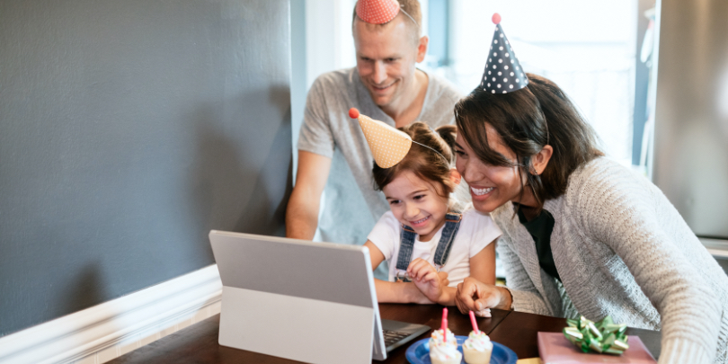 photo of parents with small girl wearing birthday hats and smiling looking at a computer