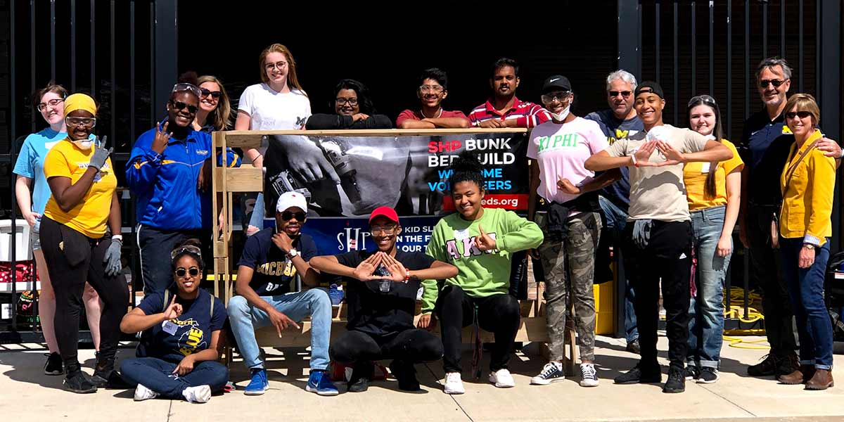 group of volunteers standing in front of bunk beds that they built