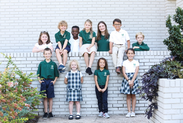photo of tallahassee classical students sitting in front of a white brick wall