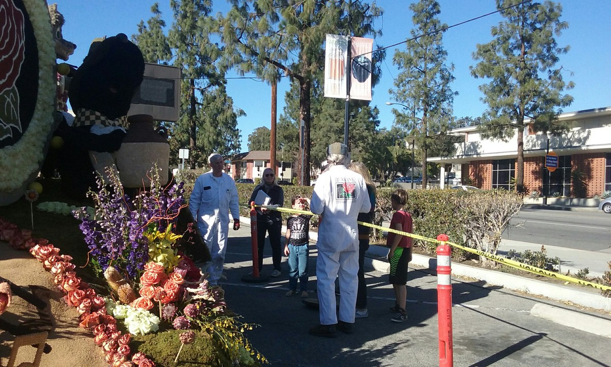 Burbank Rose Bowl volunteers standing outside next to a float blocked off by caution tape
