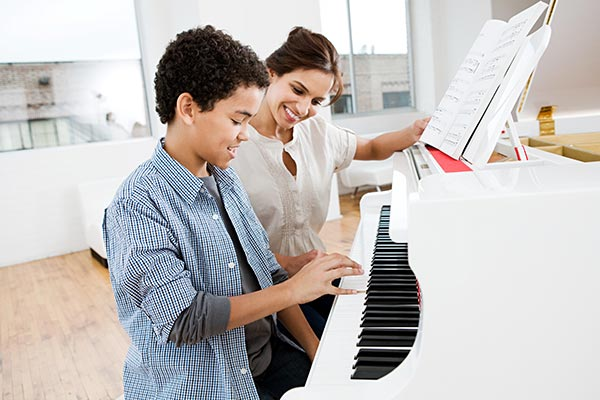 piano teacher sitting with student at piano teaching music lessons