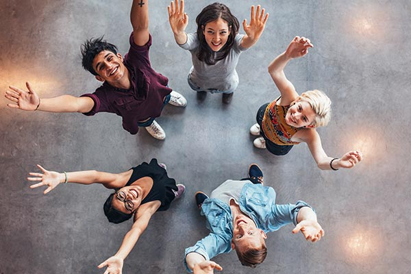 youth teens standing in circle with hands uplifted and smiling