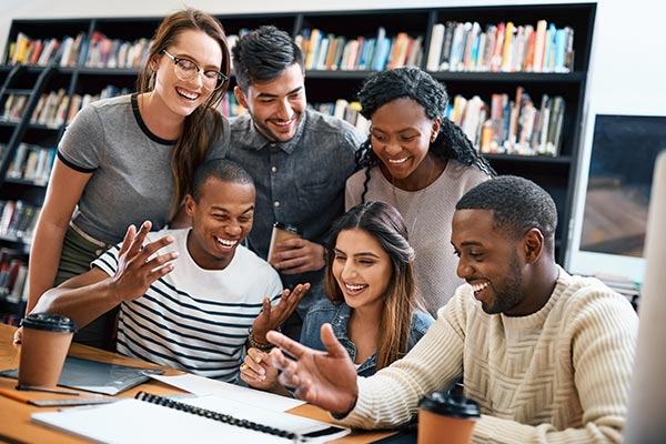 group of college students smiling in library