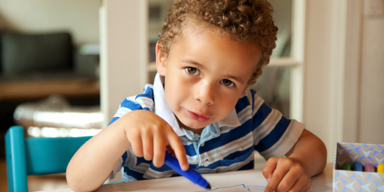 photo of little boy holding a blue crayon