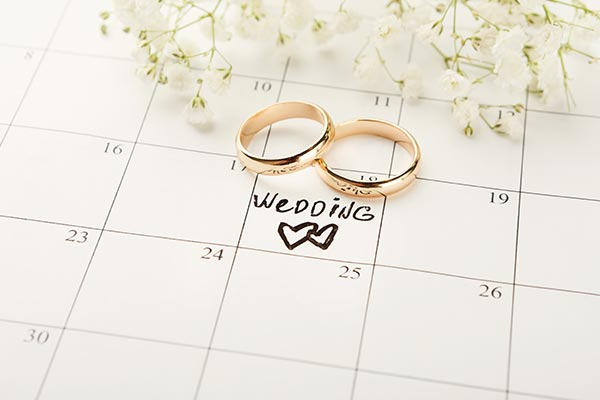 two wedding rings laying on planning calendar