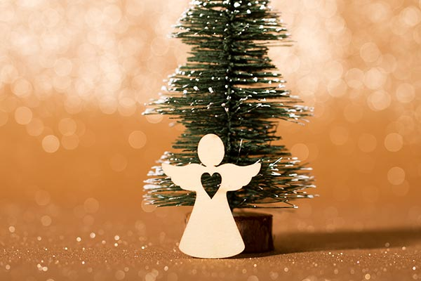 angel shaped cut out in front of small christmas tree