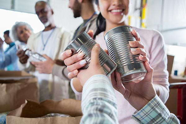 handing canned food to a collector