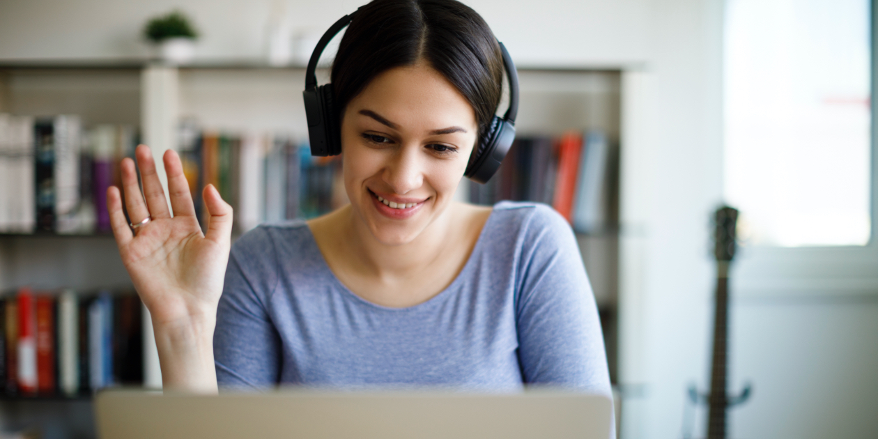 photo of woman with headphones waving at a laptop