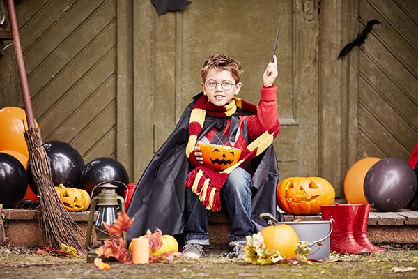 boy in halloween costume holding a pumpkin candy bowl
