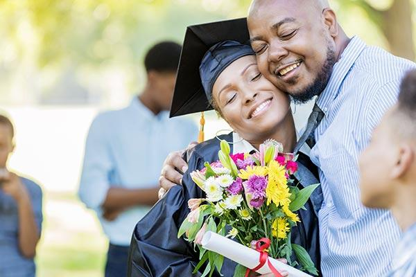 dad giving gift hugging graduate